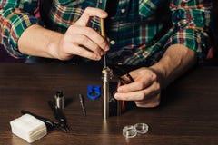 Man repairing e-evaporator. Maintenance of electronic mech mod vaping device.Modern vaporizer e-cig gadget to vape glycerin e-liquid.Vaper device repair service stock image