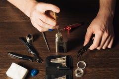 Man repairing e-evaporator. Maintenance of electronic mech mod vaping device.Modern vaporizer e-cig gadget to vape glycerin e-liquid.Vaper device repair service stock photo