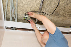 Man repairing electrical wiring on ceiling Stock Photography