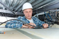 Man repairing electrical wiring on ceiling. Man repairing electrical wiring on the ceiling Royalty Free Stock Photography