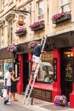 Man repairing the facade of the traditional english pub. Bath, E Royalty Free Stock Photos