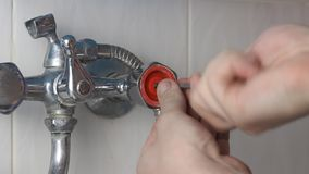 The man is repairing the faucet, close-up. 