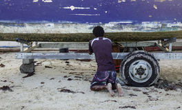 A man repairing the fishing boat on beach Stock Photo