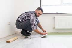 Worker man is repairing the floor in the house, laminate flooring in the style of old boards. Man is repairing the floor in the house, laminate flooring in the Stock Photography