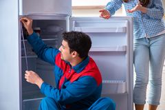 The man repairing fridge with customer. Man repairing fridge with customer Stock Photos