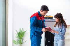 The man repairing fridge with customer. Man repairing fridge with customer Stock Photography