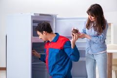 The man repairing fridge with customer. Man repairing fridge with customer Stock Images