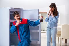 The man repairing fridge with customer. Man repairing fridge with customer Royalty Free Stock Photos
