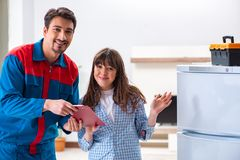 The man repairing fridge with customer. Man repairing fridge with customer Royalty Free Stock Photography