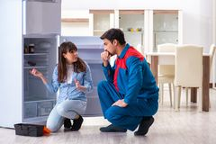 The man repairing fridge with customer. Man repairing fridge with customer Royalty Free Stock Images