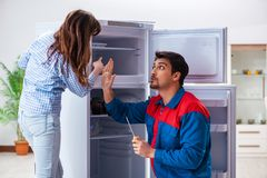 The man repairing fridge with customer. Man repairing fridge with customer Stock Photo