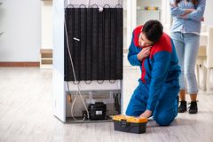 The man repairing fridge with customer. Man repairing fridge with customer Royalty Free Stock Image