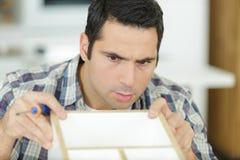 Man repairing a furniture. Man royalty free stock photos