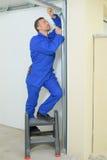 Man repairing garage door frame Royalty Free Stock Image