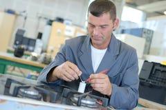Man repairing gas hob. Repair royalty free stock photo