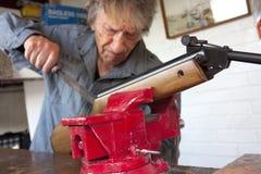 Man repairing a gun in his workshop. Elderly man in his 80's repairing a rifle gun in his workshop Stock Photography