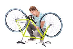 The man repairing his bike isolated on white background stock photos