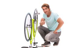 The man repairing his bike isolated on white background stock image