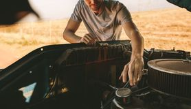 Man repairing his car on highway. Man repairing his car opening the hood. Man fixing his car on highway on a road trip to country side Royalty Free Stock Images