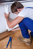 Man repairing home radiator Royalty Free Stock Image