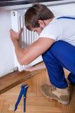 Man repairing home radiator royalty free stock image