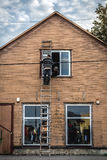 Man repairing house. Man repairing wooden house on ladder Royalty Free Stock Images