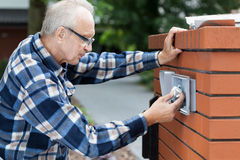 Man repairing intercom at the gate Royalty Free Stock Photography
