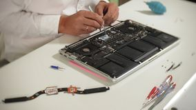 A man is repairing a laptop. The concept of computer repair. Close up of man repair laptop motherboard with a. Screwdriver. Maintenance of the hardware of the stock video