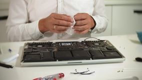 A man is repairing a laptop. The concept of computer repair. Close up of man repair laptop motherboard with a. Screwdriver. Maintenance of the hardware of the stock video footage