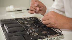 A man is repairing a laptop. The concept of computer repair. Close up of man repair laptop motherboard with a. Screwdriver. Maintenance of the hardware of the stock footage