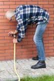 Man repairing leaky garden hose spigot Stock Image