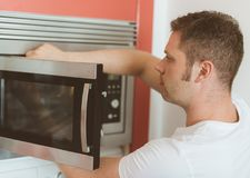 Man repairing microwave oven. Royalty Free Stock Image