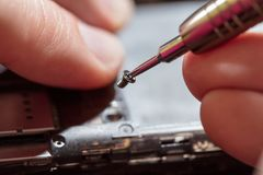 Man Repairing A Mobile phone. Close-up of a male hands servising broken smartphone royalty free stock image