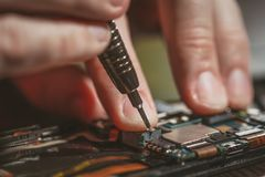 Man Repairing A Mobile phone. Close-up of a male hands servising broken smartphone stock photos