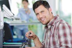 Man repairing office photocopier stock image