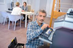 Man repairing office photocopier. Office Stock Photos