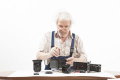 Man repairing an old camera. Male repairing an old camera at his workplace on white background Royalty Free Stock Photo