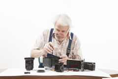 Man repairing an old camera. Male repairing an old camera at his workplace on white background Royalty Free Stock Image