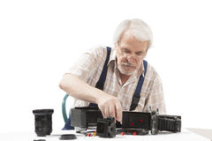 Man repairing an old camera. Male repairing an old camera at his workplace on white background Stock Photo
