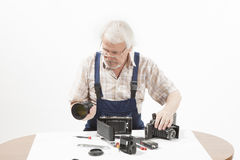 Man repairing an old camera. Male repairing an old camera at his workplace on white background Royalty Free Stock Photos