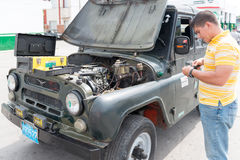 Man repairing an old Russian Jeep in Cuba streets Stock Image