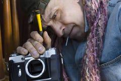 Man Repairing Photo Camera. Service man with a screwdriver repairing a photo camera, closeup cropped shot Royalty Free Stock Image