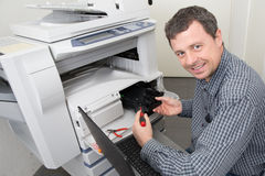 Man  repairing a printer at business place at work Royalty Free Stock Images