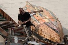 Man repairing a rowing boat stock image