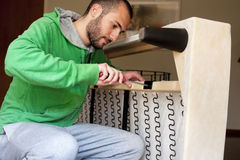 Man repairing a sofa. Closeup of a young man repairing a sofa Stock Photos
