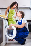 Man repairing washing machine and woman Stock Photography