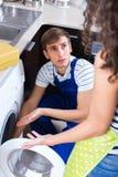 Man repairing washing machine and woman Stock Photography
