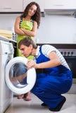 Man repairing washing machine and woman Royalty Free Stock Photos