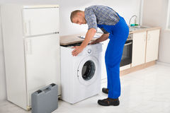 Man Repairing Washing Machine Stock Photography