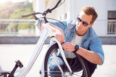 Man repairing a wheel on his bike Royalty Free Stock Images